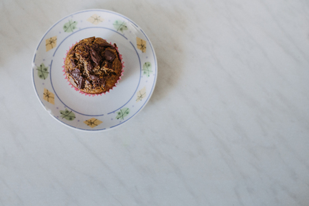 carob muffin on a white plate in minimalistic composition