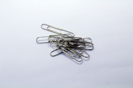 A pile of paper clip or paperclip, used to hold sheets together. Made of wire.