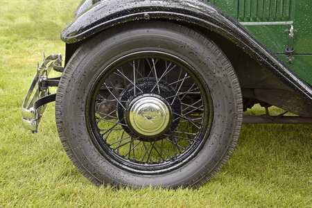 polished: The front wheel of an old car that is all polished up