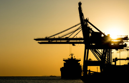 crane: Silhouette of container cargo and crane bridge Stock Photo