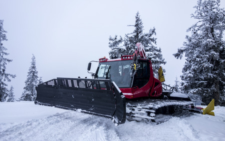 snow grooming machine: Piste Machine before snow-covered trees