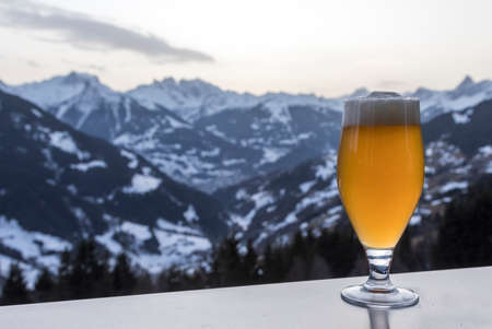 Glas of weissbeer with the alps in background Stock Photo