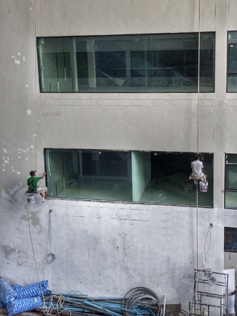 building external: Constructions workers are painting building external wall
