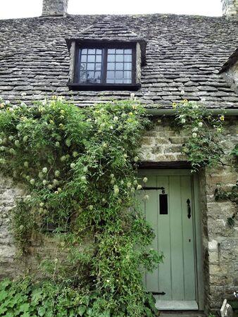 puerta verde: Casa de piedra con puerta verde y hiedra, Cotswold Foto de archivo