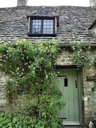 cotswold: Stone house with green door and ivy , Cotswold  Stock Photo