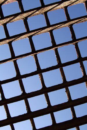 prison system: metal grille on blue sky background