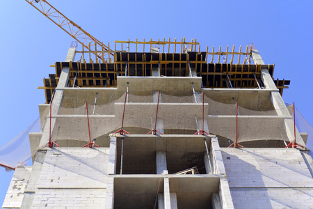 condominiums built: bottom view of the construction of highrise frame house Stock Photo