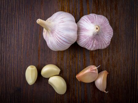 garlic cloves: Composition with garlic and garlic cloves on a dark board top view Stock Photo