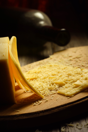 shredded cheese: shredded cheese on a wooden board and a bottle of wine. dark still life Stock Photo