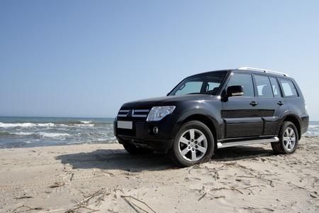 Off-road car on sand on seacoast