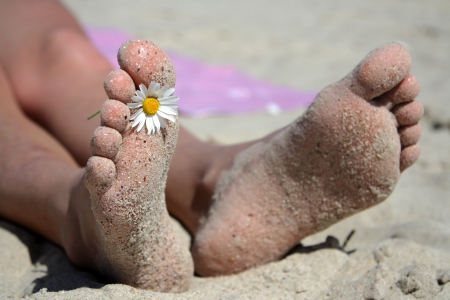 Beyaz kumlu plaj ve güneşli mavi gökyüzü karşı bir şezlong üzerinde iki ayak tatil kavramı.