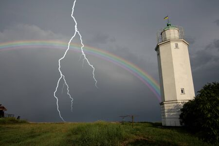 Rainbow against a lighthouse after a thunder-storm with lightning flash photo