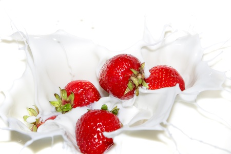 Falling a strawberry with milk splashes