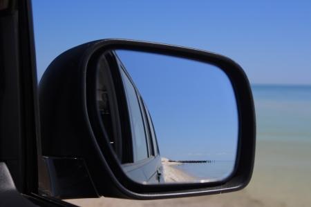 Reflexion von einem einsamen Strand in ein Auto Spiegel