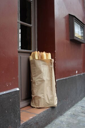 Package with a fresh baguette on a house threshold