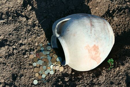 Scattered coins from the ancient jug laying on the earth  photo
