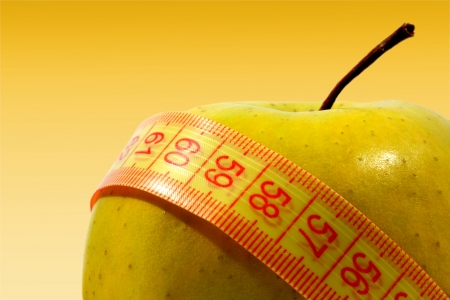 Apple wrapped up by a measuring tape