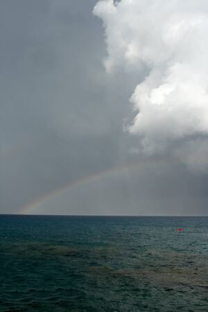 Rainbow on seacoast after a summer thunder-storm photo