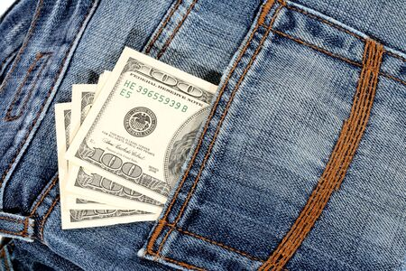 100 dollar bill sticking out from a blue jean pocket photo