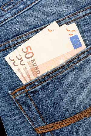 Euro bill sticking out from a blue jean pocket photo