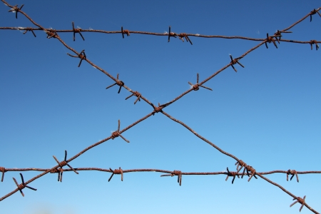 Barbed wire tense on a fence against the blue sky Stock Photo - 16099756