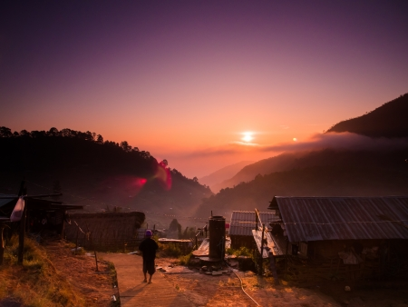 hill: Beautiful mountain and sunrise scene at hill tribe village with a walking man Stock Photo