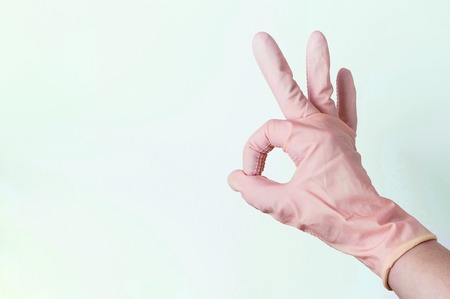 A Female hand in rubber gloves shows the sign OK on a white background Banco de Imagens - 122021024