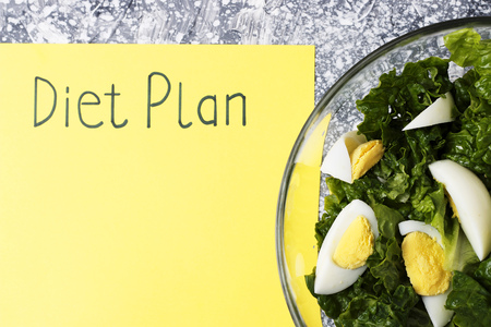 An Inscription Diet plan on yellow sheet and salad. View from above