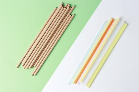 A bamboo and plastic straws for drinking on a colorful background, concept alternative