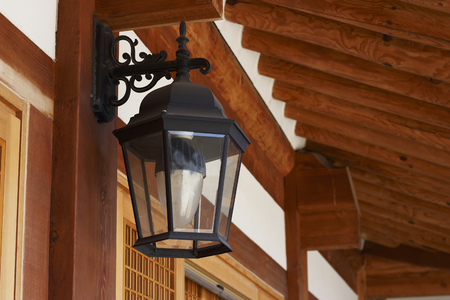 A black vintage lantern on the background of a wooden house
