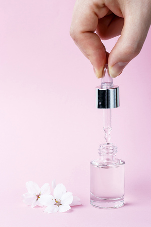 Female hand and dropper on a pink background, natural cosmetics concept Standard-Bild