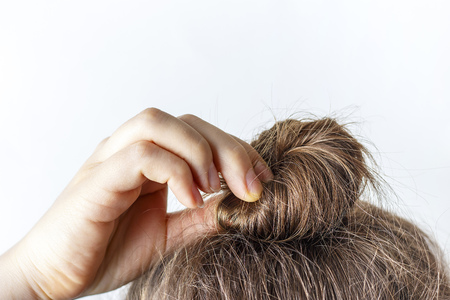 Female hand correct the bun on a white background. Modern fast hairstyle. Stockfoto