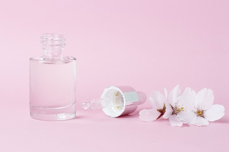 A serum and dropper on a pink background close up Archivio Fotografico