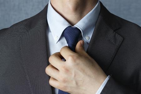 L'uomo in giacca e cravatta raddrizza la cravatta da vicino, vista frontale