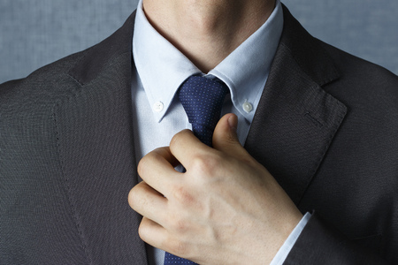 Mann im Anzug glättet Krawatte hautnah, Vorderansicht
