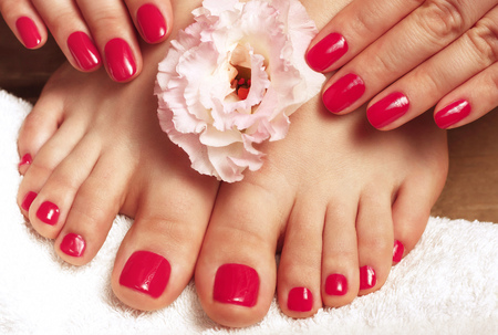 Pink manicure and pedicure with flower close up on a white background, top view