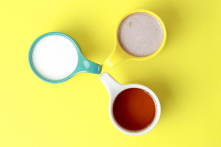 Milk, tea and hot chocolate in colorful circles on a yellow background Stock Photo