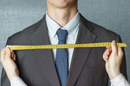 The tailor measures the suit with a measuring tape close up