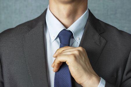 Man in suit straightens tie close up, front view Foto de archivo