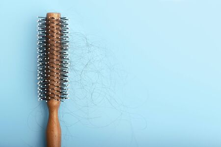 Wooden comb with fallen hair on a blue background a concert of hair loss.