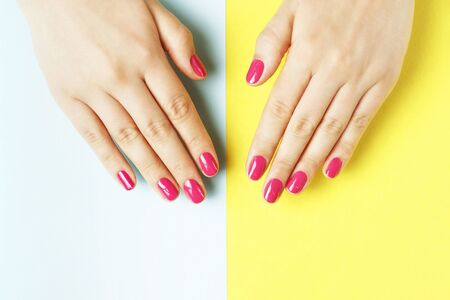 A female hands with pink manicure on yellow and blue background Stock Photo