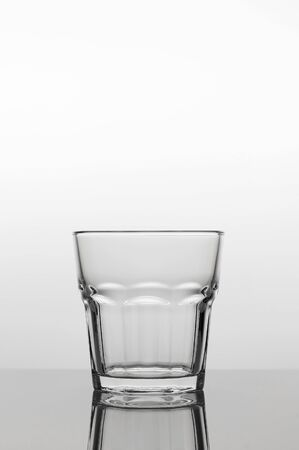 Empty transparent glass on a light background, close up