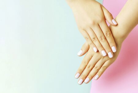 Female hands with a white manicure on a pink and blue background, top view
