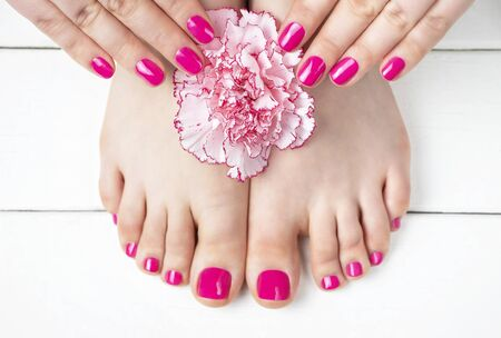 Pink manicure and pedicure with a flower on a white wooden background, top view.