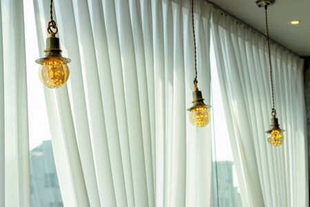 Electric lamps hang in a cafe near the window, interior details.