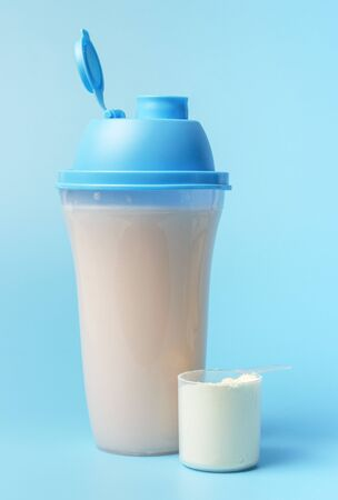 A protein shake and a scoop on a blue background, front view. Stock Photo