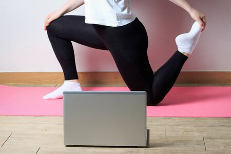 The girl in sporting black pants and white shirt makes a stretch in front of the laptop