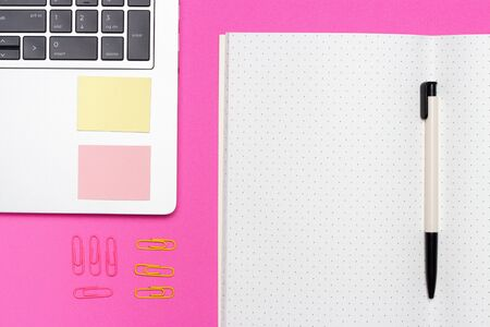 Laptop, copybook and pen on a pink background, the concept of a modern workspace