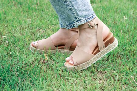 Women's feet in summer brown sandals against the background of green grass, the concept of summer shoes