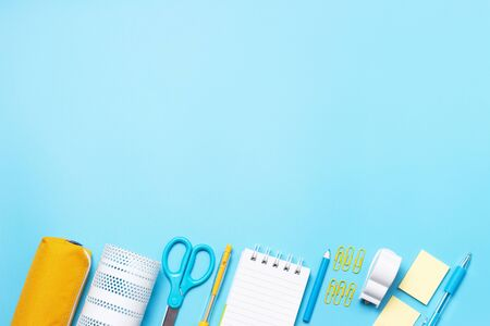 Stationery, scissors and notepad on blue background a copy of the space Imagens